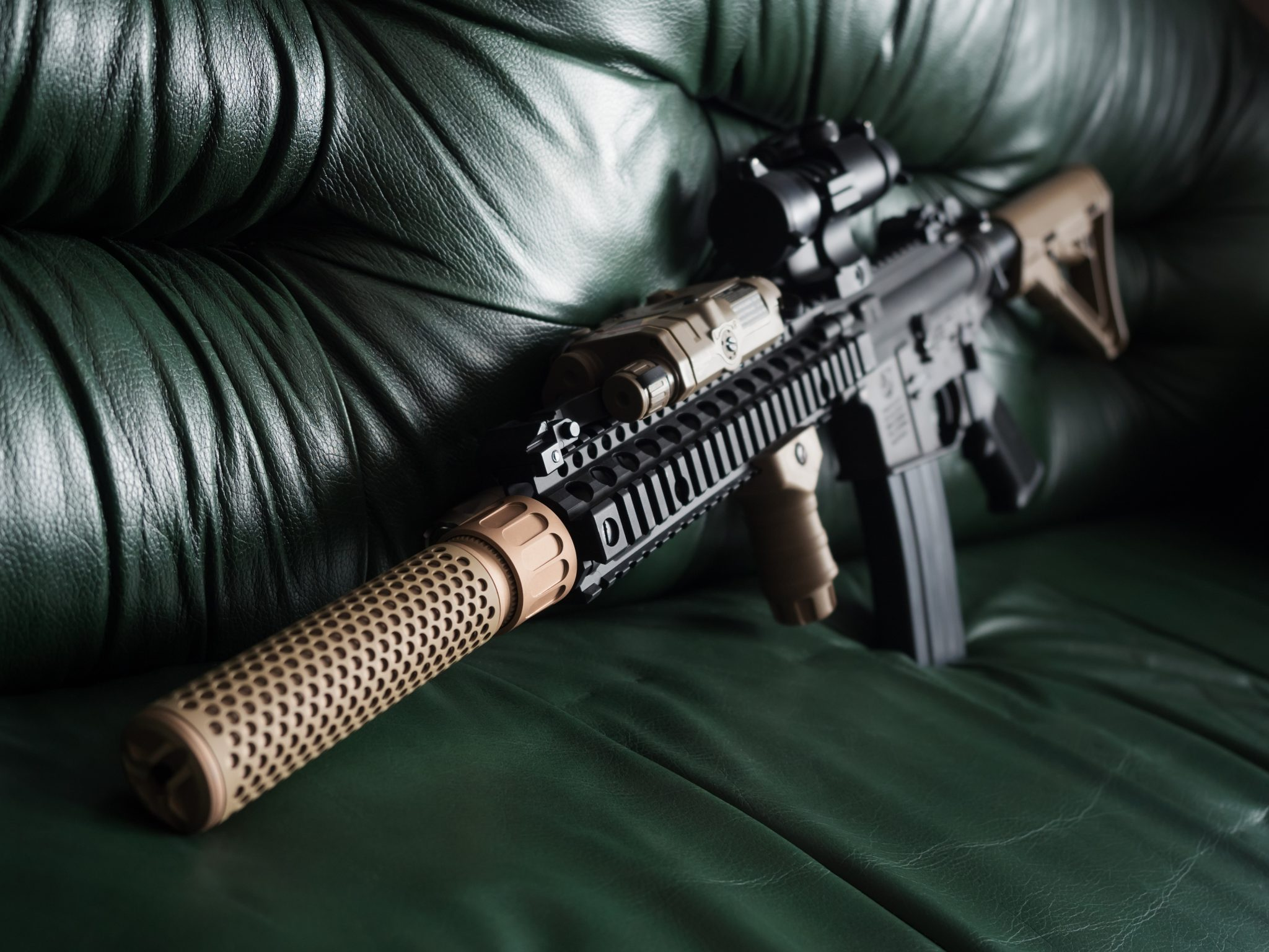 Black Rifle with suppressor On Sofa to illustrate how to buy a suppressor