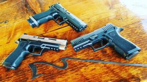 three guns on a wooden table to illustrate or approach to gun sales