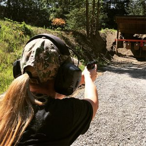 Woman shooting a firearm at a training class offered by Sporting Systems