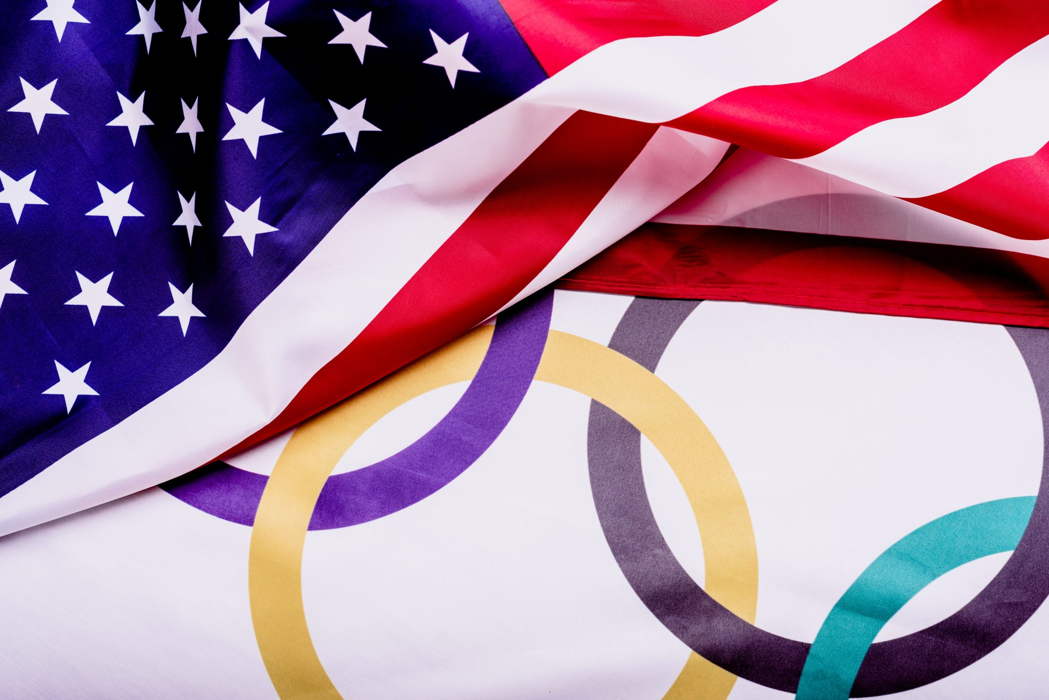 Flag of the United States folded over the Olympic rings to illustrate USA Olympic Shooting Team Earns Six Medals
