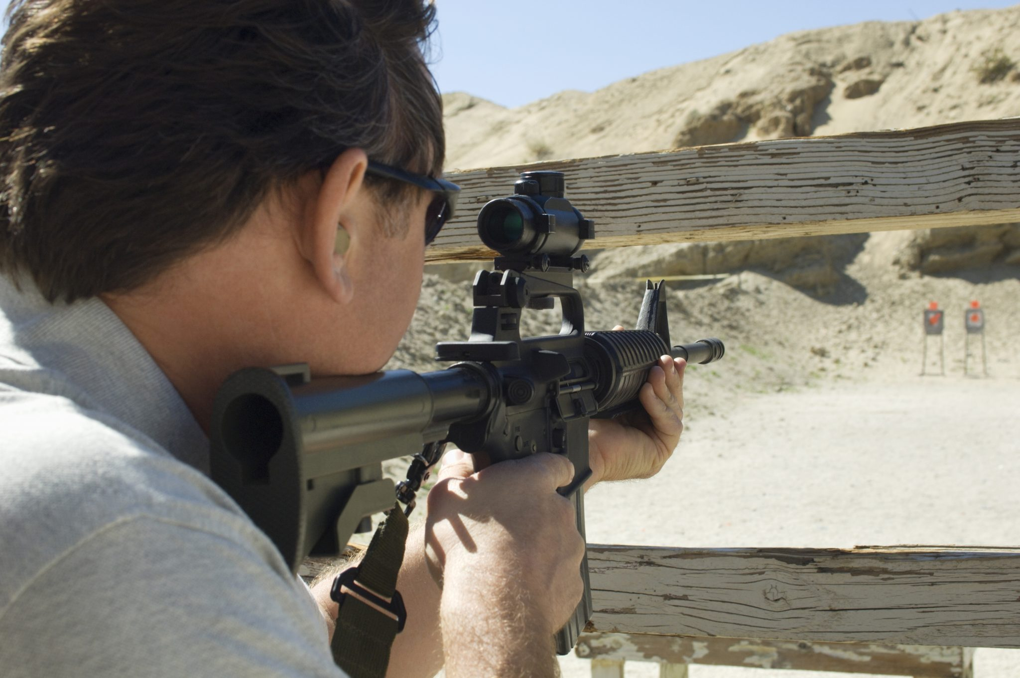 man shooting a rifle at a shooting range to illustrate What is an NFA weapon